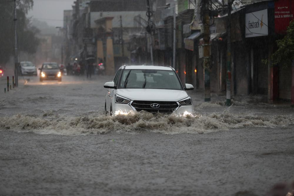 A car moves through a flooded street during monsoon rains Jammu, India, Monday, July 12, 2021. India's monsoon season runs from June to September.