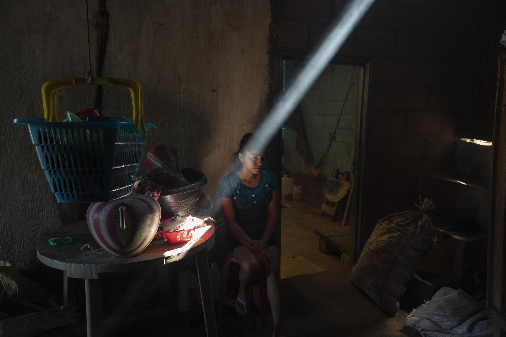 Delmi Jeronimo, the niece of Alvina Jeronimo Perez, sits in Jeronimo's kitchen before breakfast in Tizamarte, Guatemala, Friday, Dec. 11, 2020. In the dry winter months, the house is dark and cold seeps through the corrugated tin roof. In the rainy season, it is hot and stifling. (AP Photo/Moises Castillo)