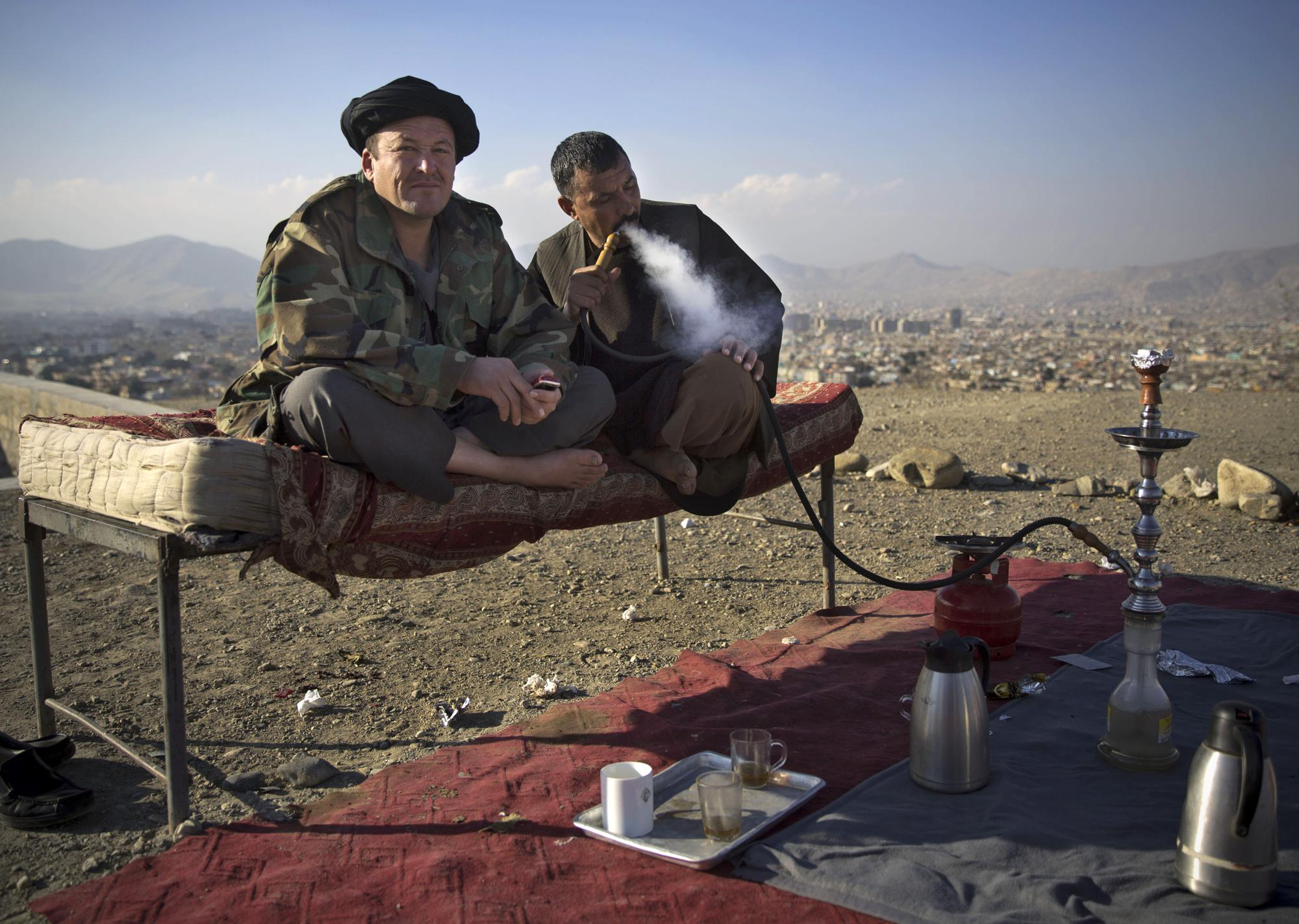 FILE - In this Nov. 25, 2013 file photo, police officers smoke a water pipe as they enjoy a quiet moment at their checkpoint overlooking Kabul, Afghanistan. (AP Photo/Anja Niedringhaus, File)