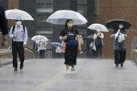 People make their way in a rain affected by a tropical storm in Sendai, Miyagi prefecture, northeast of Tokyo Wednesday, July 28, 2021. Nepartak, the season's eighth typhoon for Japan, brought strong winds and heavy rain to Japan's northern coast Wednesday after moving away from the Tokyo region and relieving the Olympic host city of a feared disruption to the games. (Kyodo News via AP)