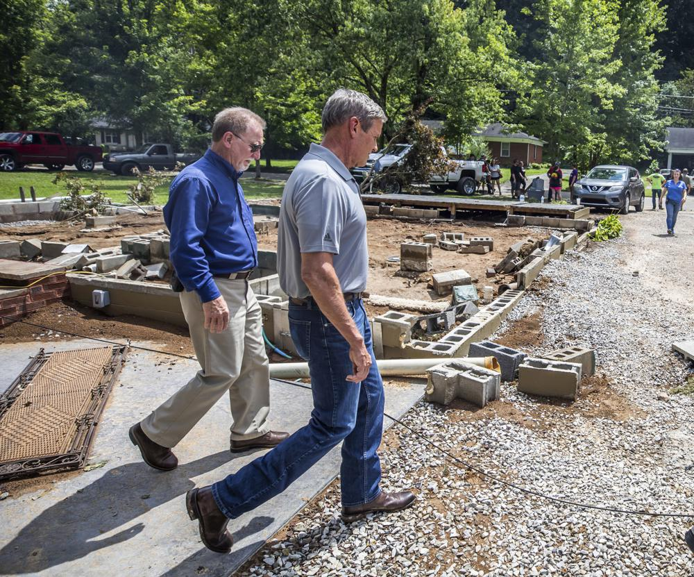 Gov. Bill Lee, right, walks past the foundation of a home that was washed away, while touring flood damage and meeting those affected, in Waverly, Tenn., Sunday, Aug. 22, 2021. (Alan Poizner/The Tennessean via AP, Pool)