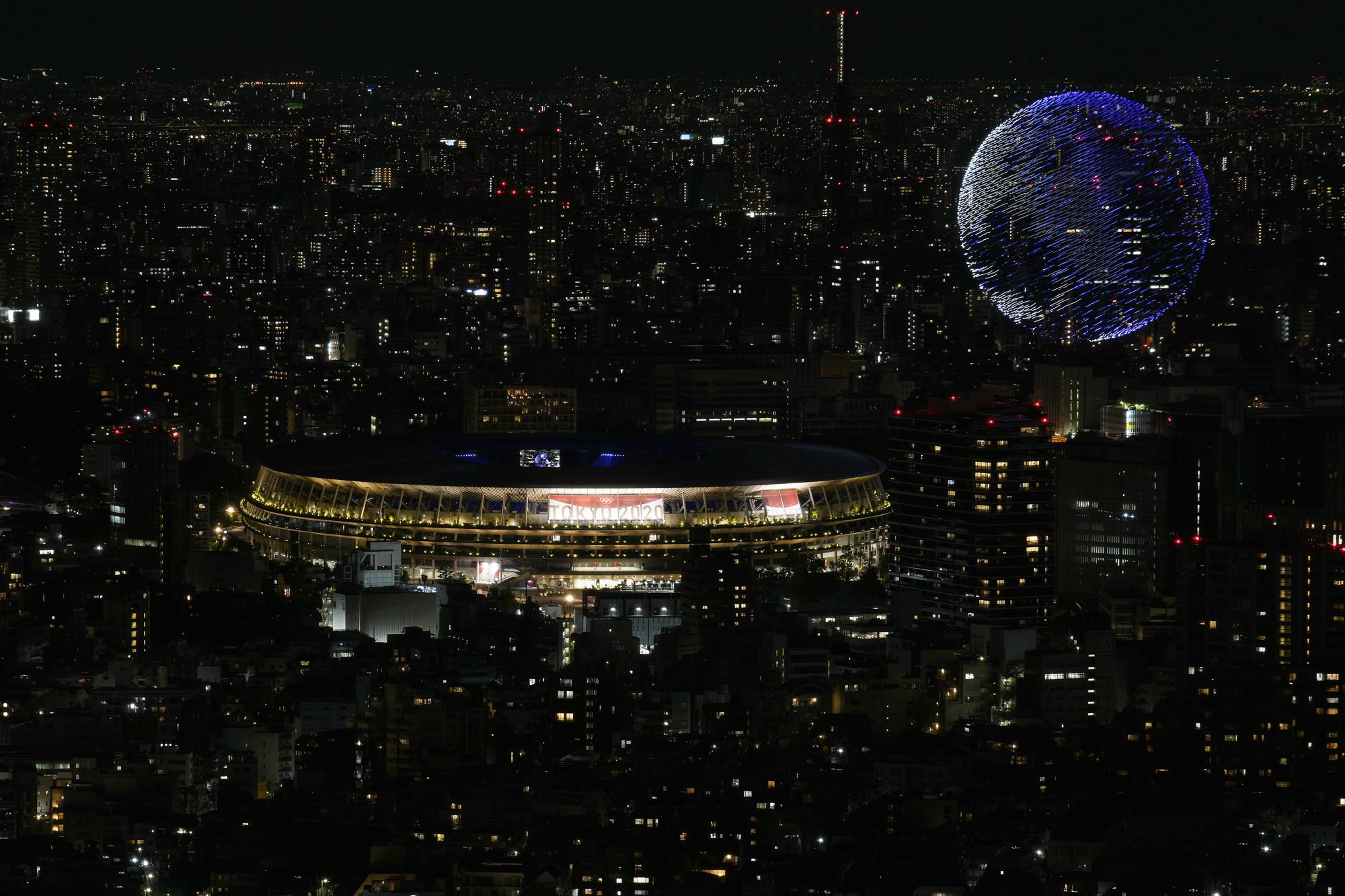 Drones fly over the National Stadium during the opening ceremony of 2020 Tokyo Olympics is seen from Shibuya Sky observation deck Friday, July 23, 2021, in Tokyo, Japan. (AP Photo/Eugene Hoshiko)
