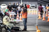 People visit a pop-up vaccination site, Tuesday, Oct. 19, 2021, in suburban Auckland, New Zealand. New Zealand reported its highest number of new coronavirus cases since the pandemic began Tuesday as an outbreak in the largest city of Auckland continued to spread. (Michael Craig/New Zealand Herald via AP)