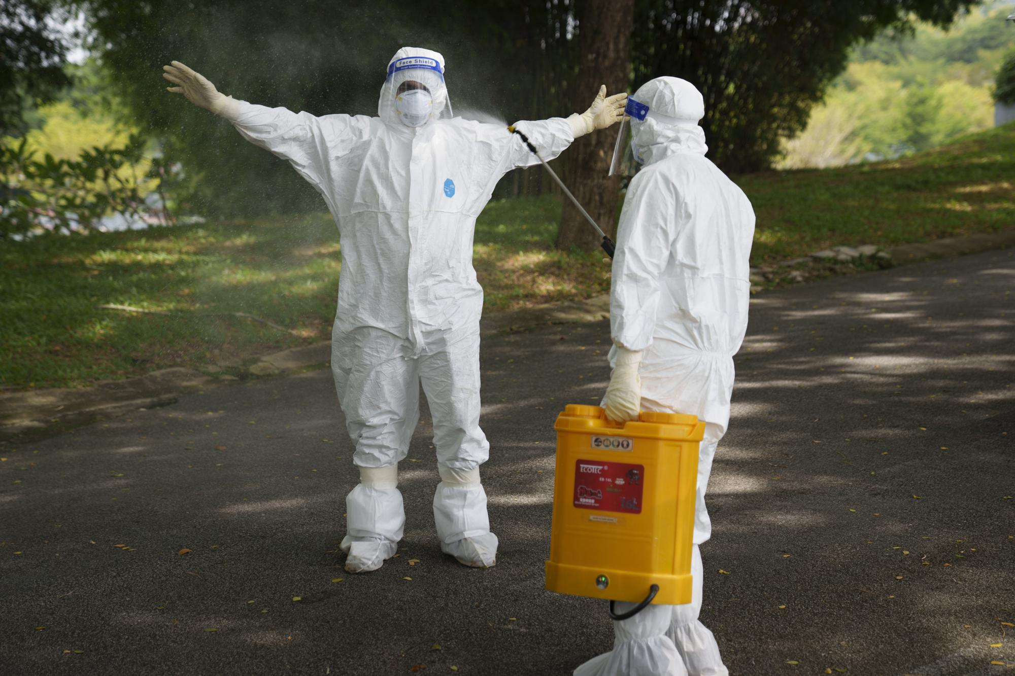 A health worker wearing Personal Protective Equipment (PPE) sanitises his colleague after the funeral for a COVID-19 victim at Nirvana memorial, a Buddhist, Taoist and Christian cemetery in Semenyih, Malaysia, Wednesday, May 26, 2021. Malaysia's latest coronavirus surge has been taking a turn for the worse as surging numbers and deaths have caused alarm among health officials, while cemeteries in the capital are dealing with an increasing number of deaths. (AP Photo/Vincent Thian)