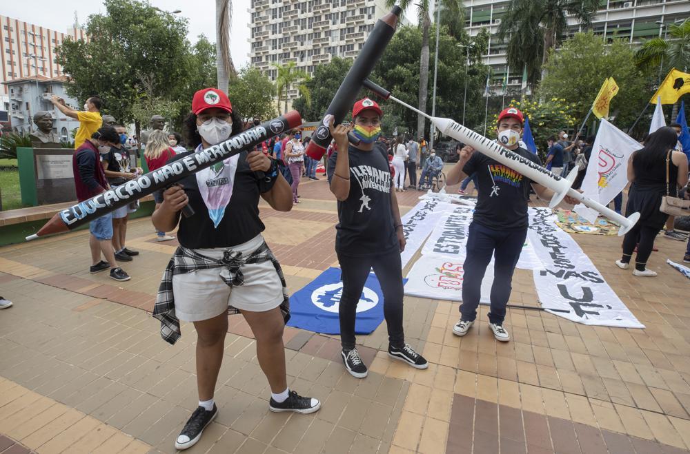 Demonstranten mit gefälschten Pistolen in Bleistiftform und einer Spritze nehmen am Samstag, den 19. , 2021. (AP Photo/Andre Penner)