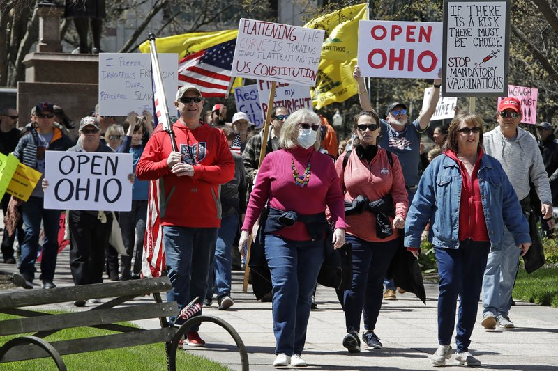 FILE-This Monday, April 20, 2020 file photo shows protesters gathering outside of the Ohio State House in Columbus, Ohio, to protest the stay home order. Legislative testimony made Wednesday, Feb. 17, 2021 in support of a GOP-backed effort to limit public health orders made by Ohio's governor was removed from YouTube after the service deemed it contained COVID-19 misinformation. The Google-owned platform said it removed content that was uploaded this week to The Ohio Advocates for Medical Freedom channel for violating the company's terms of services. (AP Photo/Gene J. Puskar, File)