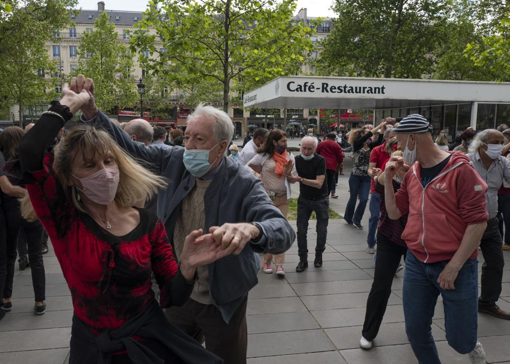 FILE - In this May 23, 2021, file photo, a couple with protective masks on dance at Republic square in Paris. Coronavirus infections, hospitalizations and deaths are plummeting across much of Europe. Vaccination rates are accelerating, and with them, the promise of summer vacations. (AP Photo/Rafael Yaghobzadeh, File)