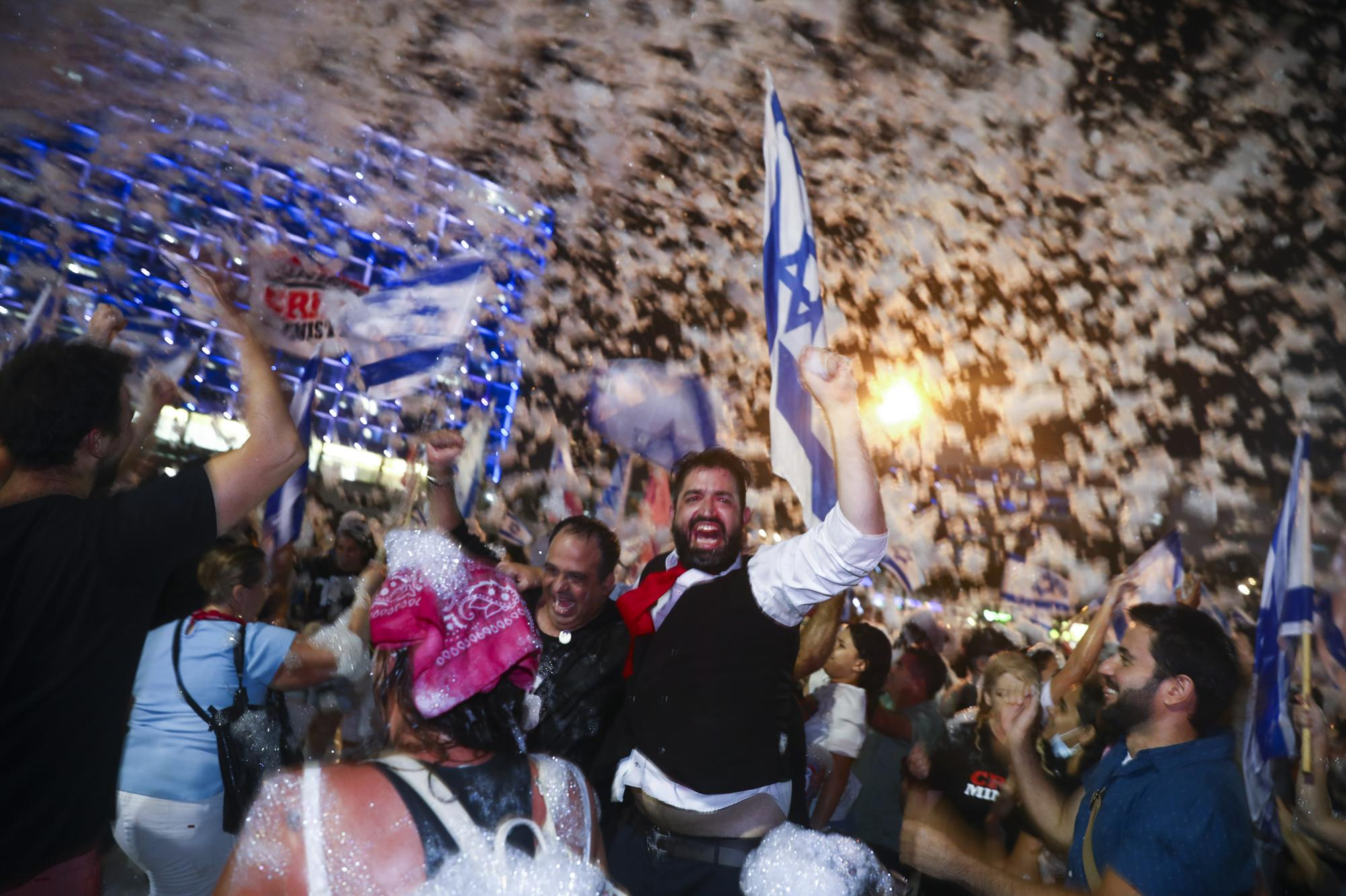 People celebrate the swearing-in of the new government in Tel Aviv, Israel, Sunday, June 13, 2021. Israel's parliament has voted in favor of a new coalition government, formally ending Prime Minister Benjamin Netanyahu's historic 12-year rule. Naftali Bennett, a former ally of Netanyahu, became the leader. (AP Photo/Oded Balilty)