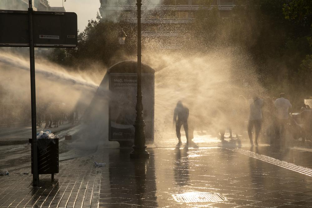 Police use tear gas and water cannons to disperse anti-vaccine protesters during a rally at Syntagma square, central Athens, on Wednesday, July 21, 2021. Authorities have openly expressed concern that slowing vaccination rates could hurt the struggling tourism industry, a mainstay of the economy, and have tightened restrictions for unvaccinated tourists and residents, banning their entry to all indoor dining and entertainment venues. (AP Photo/Yorgos Karahalis)