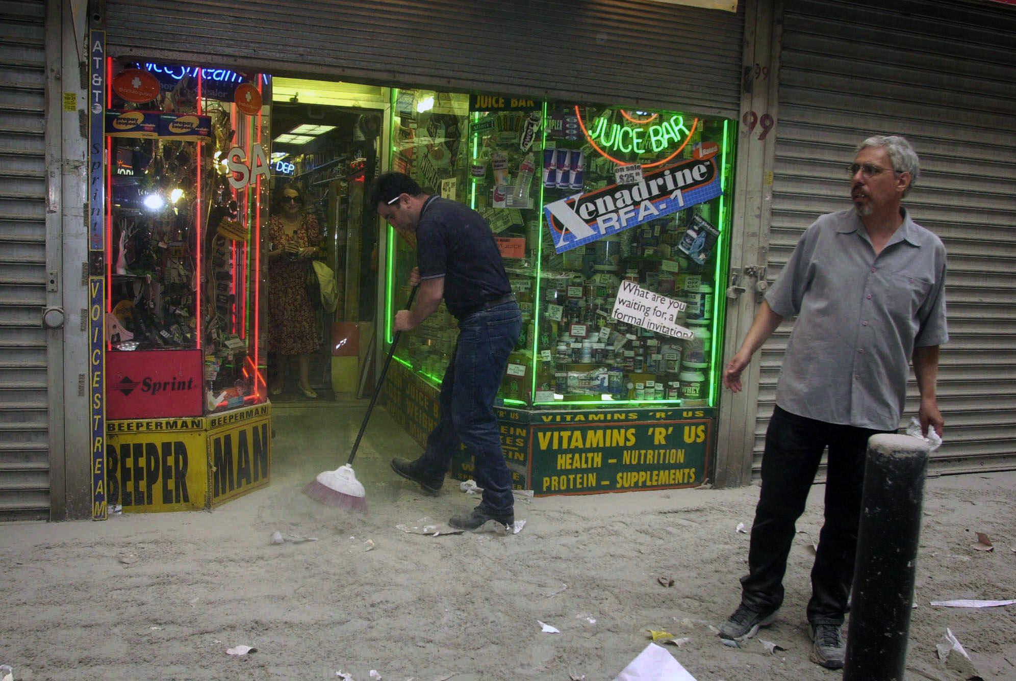 Harry Shasho sweeps up before being evacuated from his vitamin store after the collapse of New York's World Trade Center on Tuesday, Sept. 11, 2001. (AP Photo/Suzanne Plunkett)