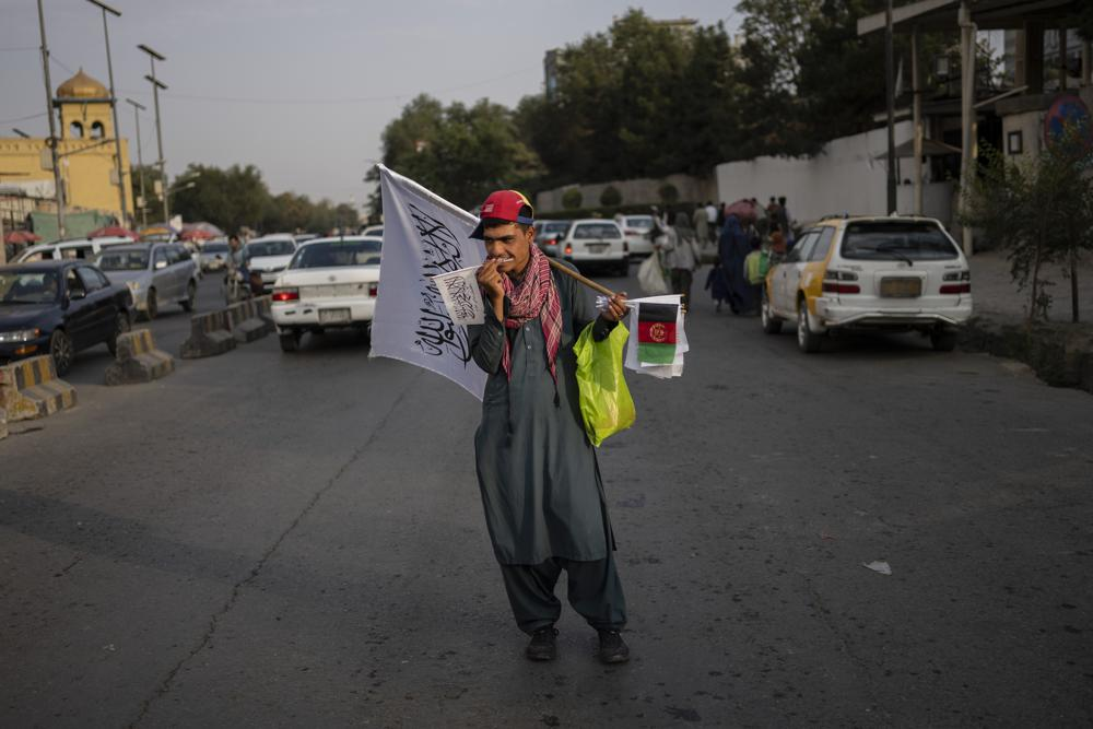 A street vendor sells Taliban and Afghan flags on a street in Kabul, Afghanistan, Thursday, Sept. 30, 2021. (AP Photo/Bernat Armangue)