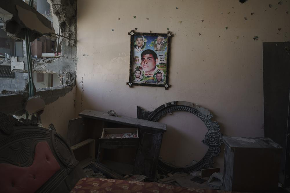 A poster with a photo of Adham Nassir, a cart driver who died in the 2008 war, hangs on the wall of his widow's house, which was heavily damaged by airstrikes in the recent 11-day war in Beit Hanoun, northern Gaza Strip, Sunday, June 13, 2021. (AP Photo/Felipe Dana)