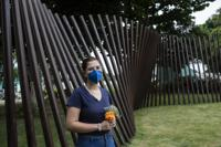 Bruna Chaves, a 25-year-old chemistry student, who lost her mother to COVID-19, poses for a photo at the Penitence Cemetery in Rio de Janeiro, Brazil, Wednesday, Oct. 27, 2021. In recent weeks, Chaves started tuning in to the Brazilian Senate committee's nationally televised investigation of the government's pandemic response. (AP Photo/Bruna Prado)