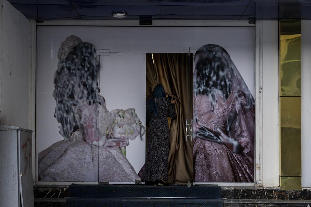 Una mujer ingresa en un salón de belleza en Kabul, Afganistán, el sábado 11 de septiembre de 2021. Desde que los talibanes asumieron el control del gobierno, diversas imágenes sobre mujeres en el exterior de salones de belleza fueron retirados o cubiertos. (AP Foto/Bernat Armangue)