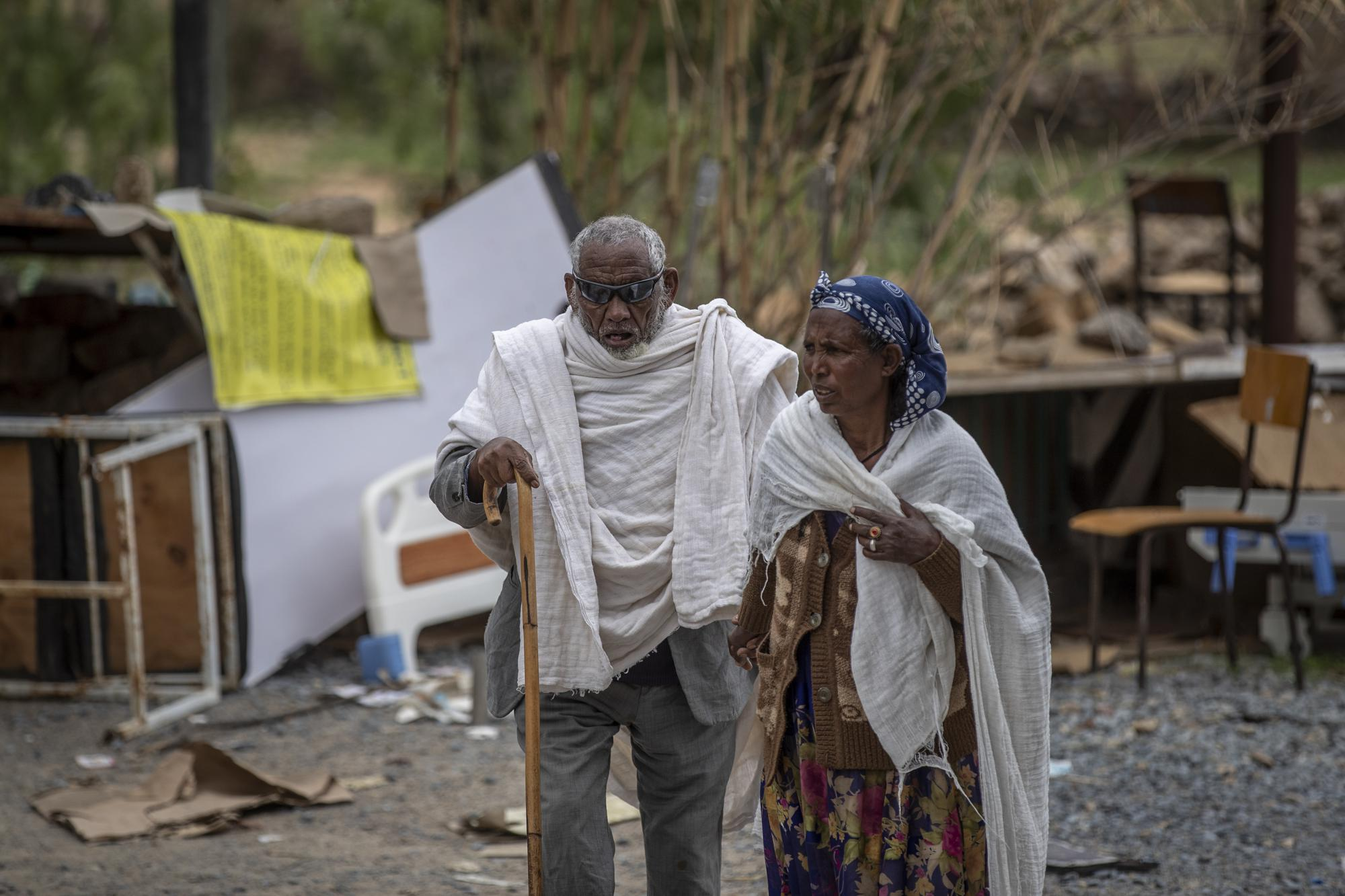 A woman leads a blind man to a visiting doctor, past destroyed furniture and other items in the driveway of a hospital which was damaged and looted by Eritrean soldiers who used it as a base, according to witnesses, in Hawzen, in the Tigray region of northern Ethiopia, on Friday, May 7, 2021. The battle for Hawzen is part of a larger war in Tigray between the Ethiopian government and the Tigrayan rebels that has led to the flightof more than 2 million of the region's 6 million people. (AP Photo/Ben Curtis)
