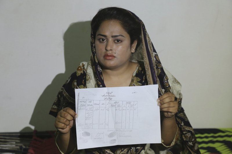 In this May 14, 2019, photo, Pakistani Christian Natasha Masih girl shows her marriage certificate during an interview in Faisalabad, Pakistan. Natasha begged her mother to bring her home from China, but it took an elaborate scheme devised by a small cabal of Christian men in her hometown of Faisalabad, in Pakistan's Punjab province, to orchestrate her escape from what began as an unhappy marriage, and ended in prostitution. (AP Photo/K.M. Chaudary)