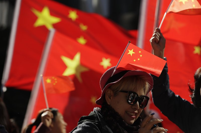 FILE - In this Dec. 7, 2019, file photo, pro-Beijing supporters wave Chinese national flags during a rally in Hong Kong. The Standing Committee of China's congress has passed amendments to a law that will criminalize the intentional insulting of the national flag and emblem, after anti-government protesters last year desecrated the Chinese flag. (AP Photo/Mark Schiefelbein, File)