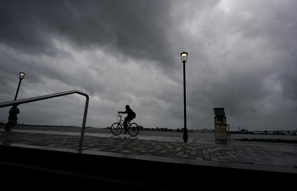 A man bikes along the Mississippi River near the French Quarter as the sun rises and the early effects of Hurricane Ida are felt, Sunday, Aug. 29, 2021, in New Orleans, La. (AP Photo/Eric Gay)