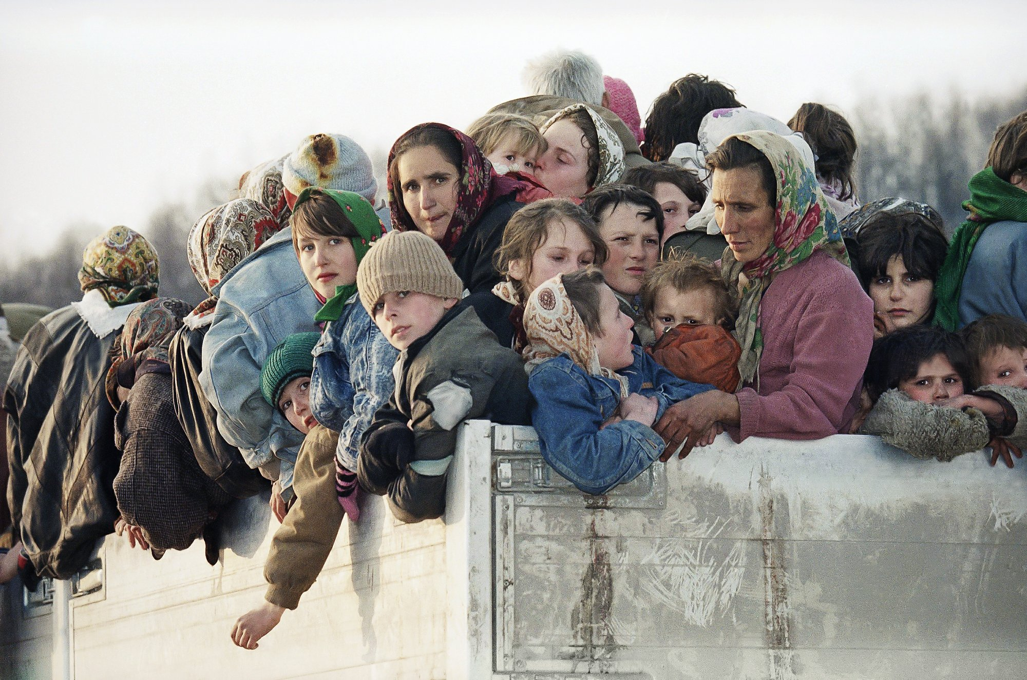 FILE- In this Monday, March 29, 1993 file picture evacuees from the besieged Muslim enclave of Srebrenica, packed on a truck en route to Tuzla, pass through Tojsici.  Survivors of the genocide in the eastern Bosnian town of Srebrenica, mainly women, will on Saturday July 11, 2020, commemorate the 25th anniversary of the slaughter of their fathers and brothers, husbands and sons.  At least 8,000 mostly Muslim men and boys were chased through woods in and around Srebrenica by Serb troops in what is considered the worst carnage of civilians in Europe since World War II. The slaughter was also the only atrocity of the brutal war that has been confirmed an act of genocide.(AP Photo/Michel Euler, File)