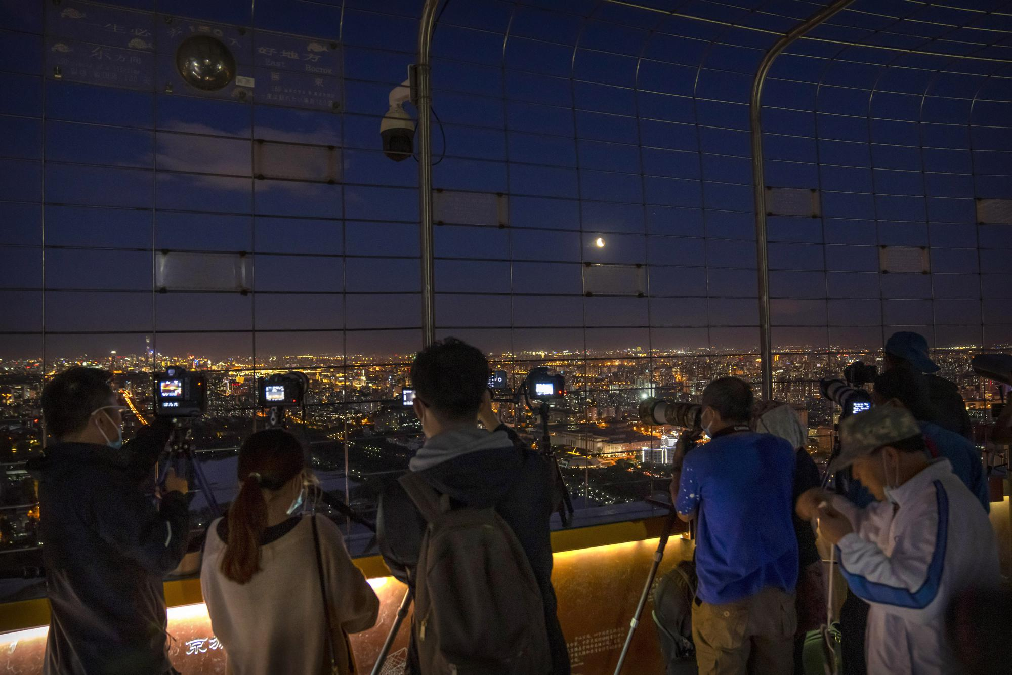 Photographers take photos of a lunar eclipse at the Central TV Tower in Beijing, Wednesday, May 26, 2021. (AP Photo/Mark Schiefelbein)