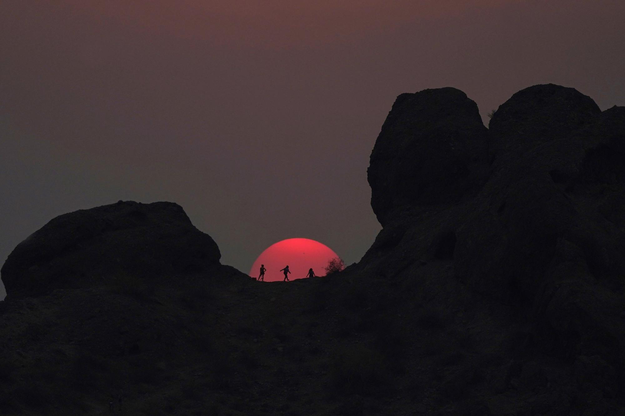 Hikers pause to watch the sunset at Papago Park during a heatwave where temperatures reached 115 degrees Fahrenheit (46 degrees Celsius) in Phoenix on Tuesday, June 15, 2021. (AP Photo/Ross D. Franklin)
