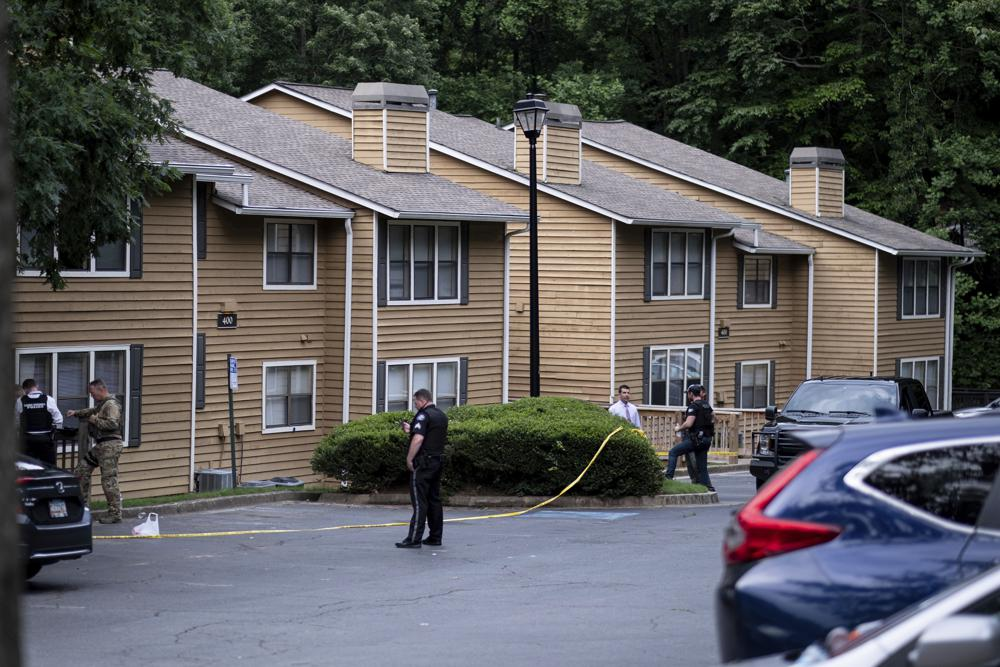 Law enforcement officers wait outside of a Sandy Springs, Ga., apartment where Gary Creek died Tuesday, June 8, 2021, following a SWAT standoff. Federal officials requested an arrest warrant Friday when Creek, 39, failed to surrender after he was named in a racketeering indictment. (AP Photo/Ben Gray)