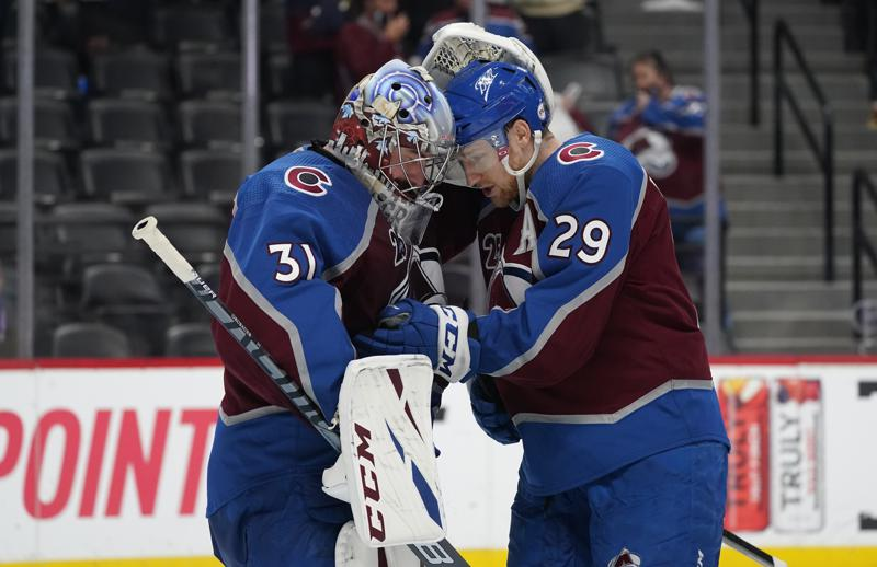 Colorado Avalanche goaltender Philipp Grubauer, left, is congratulated by center Nathan MacKinnon after Game 2 of the team's NHL hockey Stanley Cup first-round playoff series against the St. Louis Blues on Wednesday, May 19, 2021, in Denver. Colorado won 6-3. (AP Photo/David Zalubowski)