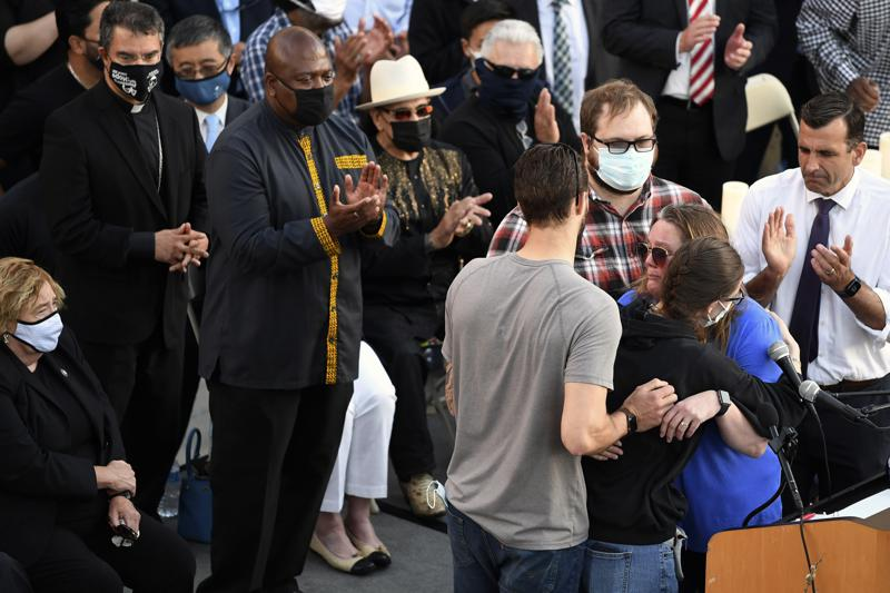 Family members of shooting victim Timothy Romo embrace during a vigil at City Hall in San Jose, Calif., Thursday, May 27, 2021, in honor of the multiple people killed when a gunman opened fire at a rail yard the day before. (AP Photo/Nic Coury)