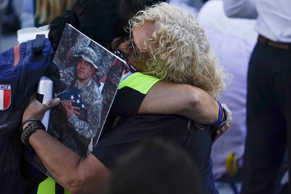 People react as they attend a ceremony marking the 20th anniversary of the Sept. 11, 2001, terrorist attacks at the National September 11 Memorial and Museum in New York, Saturday, Sept. 11, 2021. (AP Photo/Evan Vucci)