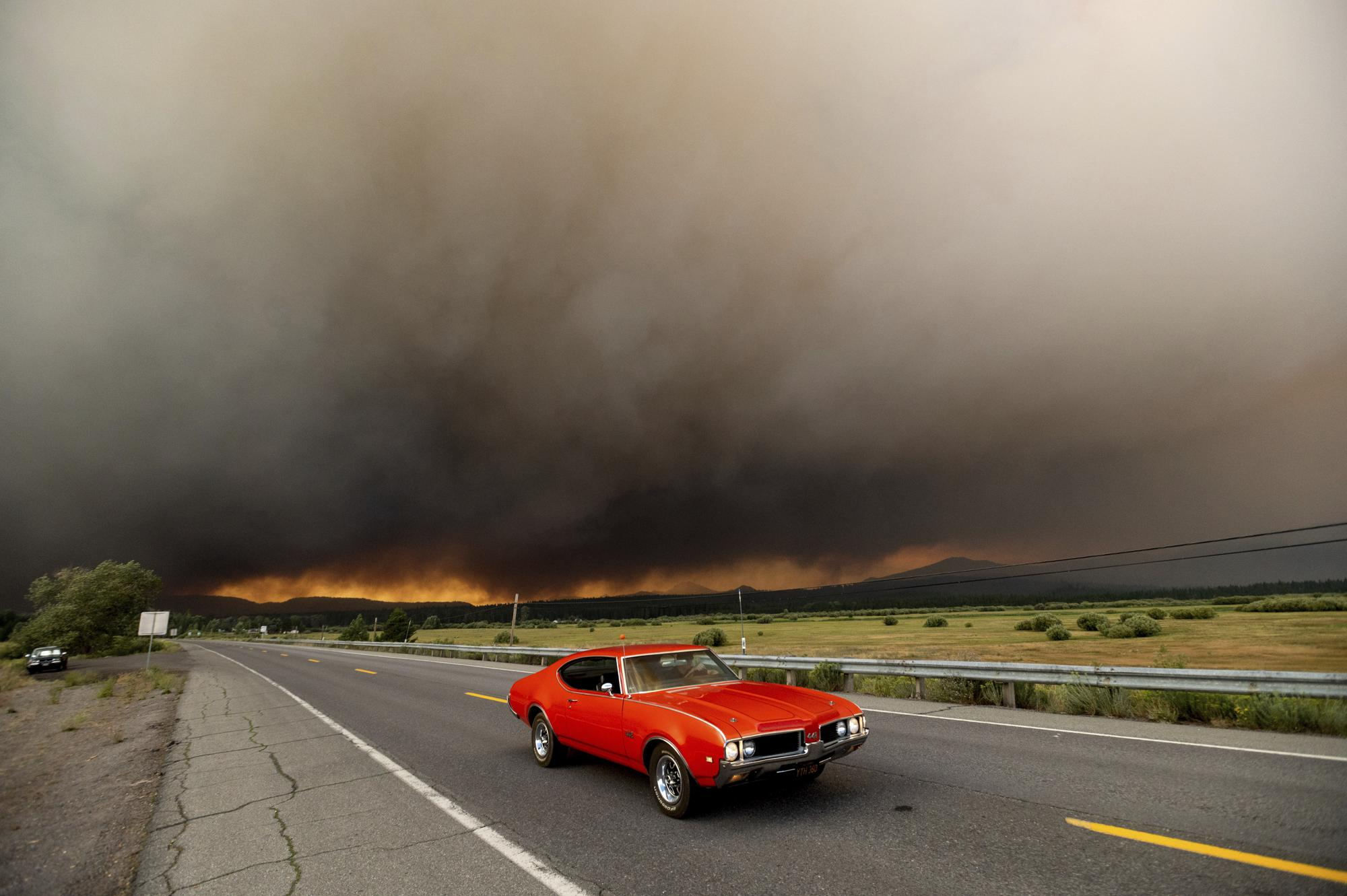 A car leaves Chester, Calif., which is under mandatory evacuation orders, as the Dixie Fire burns on the edge of town on Wednesday, Aug. 4, 2021. The region is under red flag fire warnings due to dry, windy conditions. (AP Photo/Noah Berger)