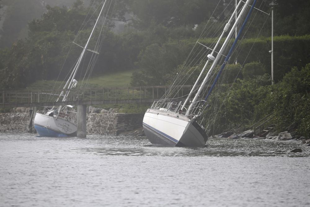 Zwei Segelboote, die sich von ihren Liegeplätzen gelöst haben und während des Tropensturms Henri auf Grund gelaufen sind, sitzen am Montag, den 23. August 2021, immer noch auf den Felsen in Jamestown, RI. (AP Photo/Stew Milne)