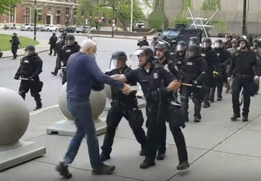 Police officer appears to shove an elderly protester who falls and cracks his head; he's in serious condition in the hospital
