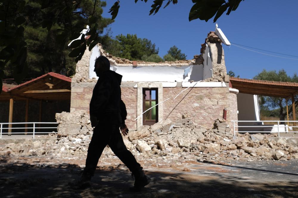 Ein Bewohner geht nach einem starken Erdbeben im Dorf Arcalochori auf der südlichen Insel Kreta, Griechenland, Montag, 27. September 2021, neben einer beschädigten griechisch-orthodoxen Kapelle vorbei. Ein starkes Erdbeben mit einer vorläufigen Stärke von 5,8 hat die südgriechische Insel Kreta und griechische Behörden sagen, dass eine Person getötet und mehrere weitere verletzt wurden.  (AP-Foto/Harry Nikos)