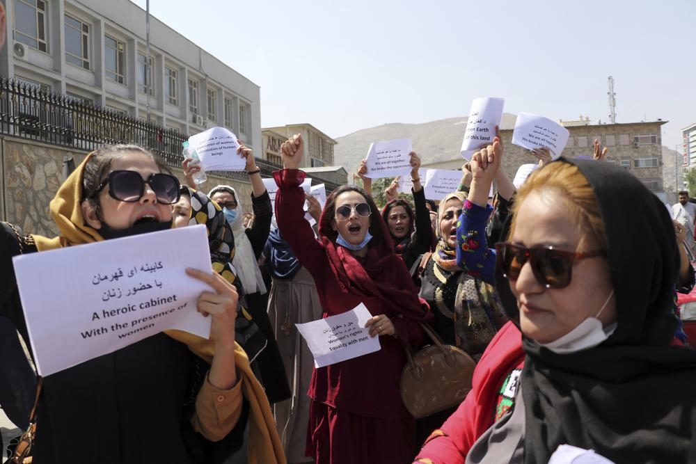 Women gather to demand their rights under the Taliban rule during a protest in Kabul, Afghanistan, Friday, Sept. 3, 2021. As the world watches intently for clues on how the Taliban will govern, their treatment of the media will be a key indicator, along with their policies toward women. When they ruled Afghanistan between 1996-2001, they enforced a harsh interpretation of Islam, barring girls and women from schools and public life, and brutally suppressing dissent. (AP Photo/Wali Sabawoon)