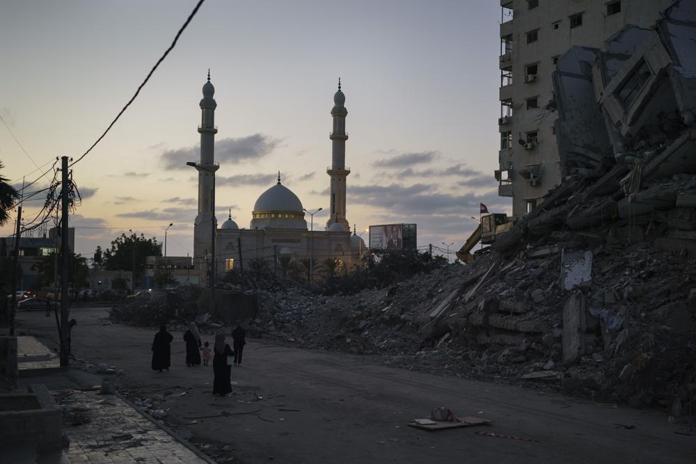 Palestinians walk next to the rubble of a building destroyed by an airstrike during an 11-day war between Israel and Hamas, the militant group that controls Gaza, in Gaza City, Thursday, June 10, 2021. (AP Photo/Felipe Dana)
