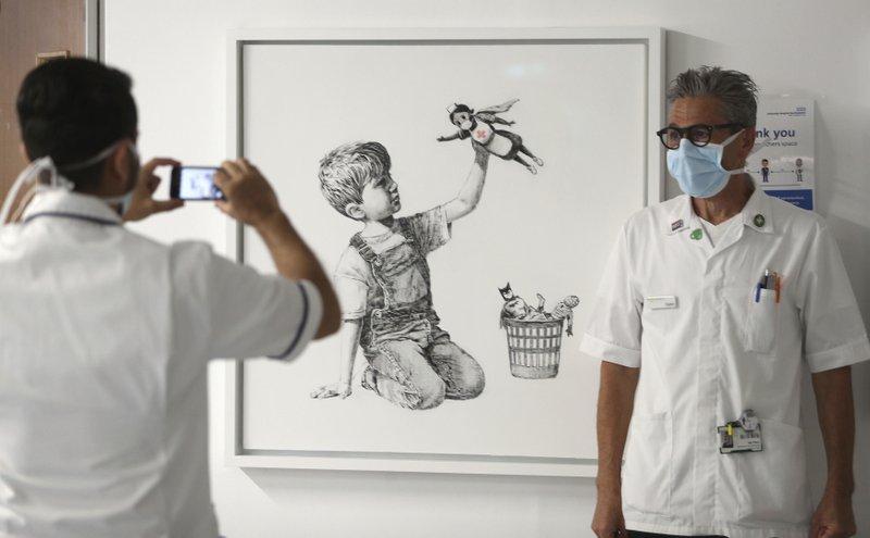 Un membre del personal sanitari es fotografia davant de l'obra de Banksy