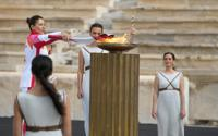 Greece's Olympic Cross Country Ski Champion Paraskevi Ladopoulou, left, lights the flame during the Olympic flame handover ceremony at Panathinean stadium in Athens, Greece, Tuesday, Oct. 19, 2021. The flame will be transported by torch relay to Beijing, China, which will host the Feb. 4-20, 2022 Winter Olympics. (AP Photo/Thanassis Stavrakis)