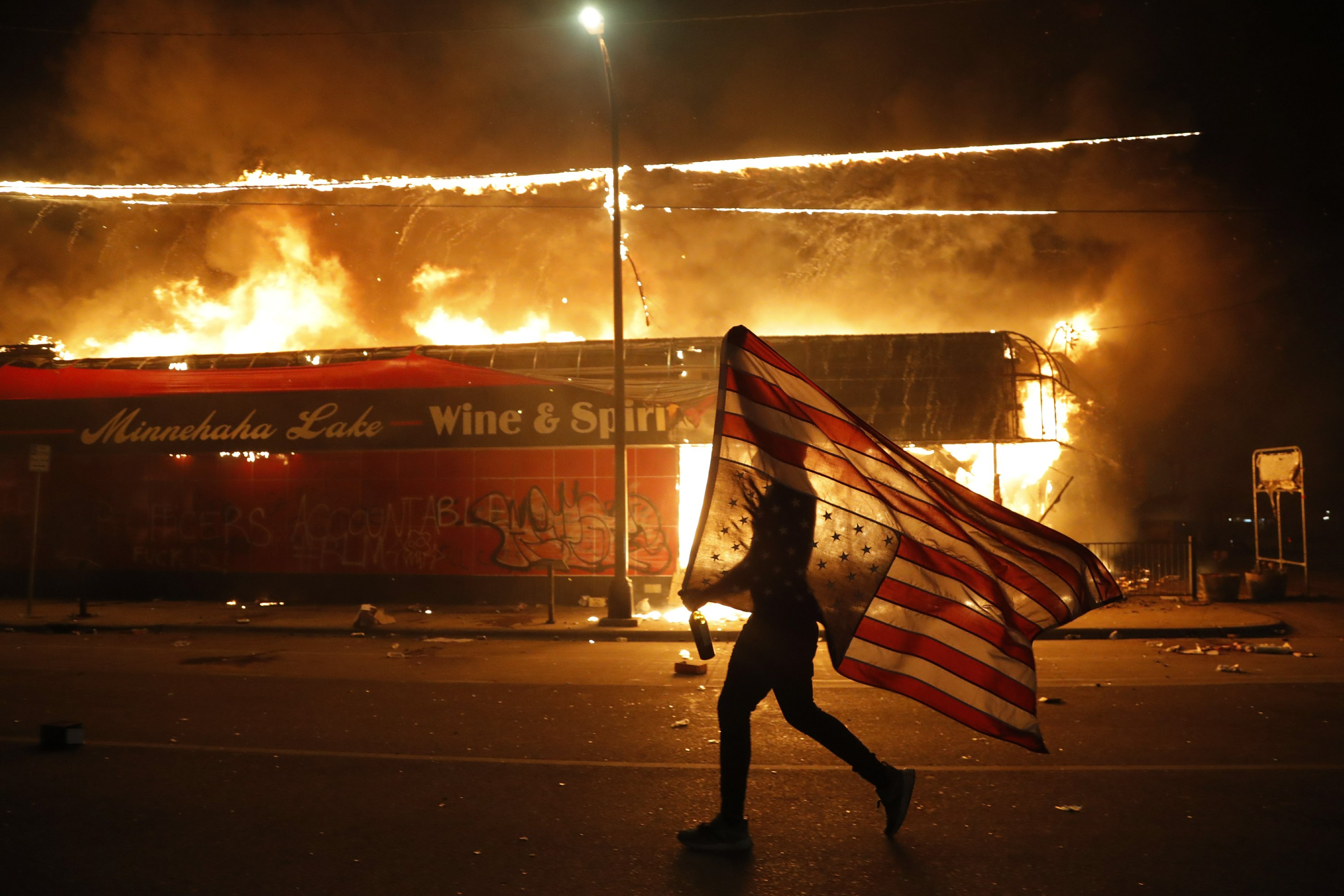AP photo of flag-bearing protester rockets around the...