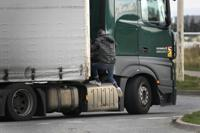 A migrant jumps on a truck in Calais, northern France, Thursday, Oct. 14, 2021, to cross the tunnel heading to Britain.  In a dangerous and potentially deadly practice, he is trying to get through the heavily policed tunnel linking the two countries by hiding on a truck. (AP Photo/Christophe Ena)