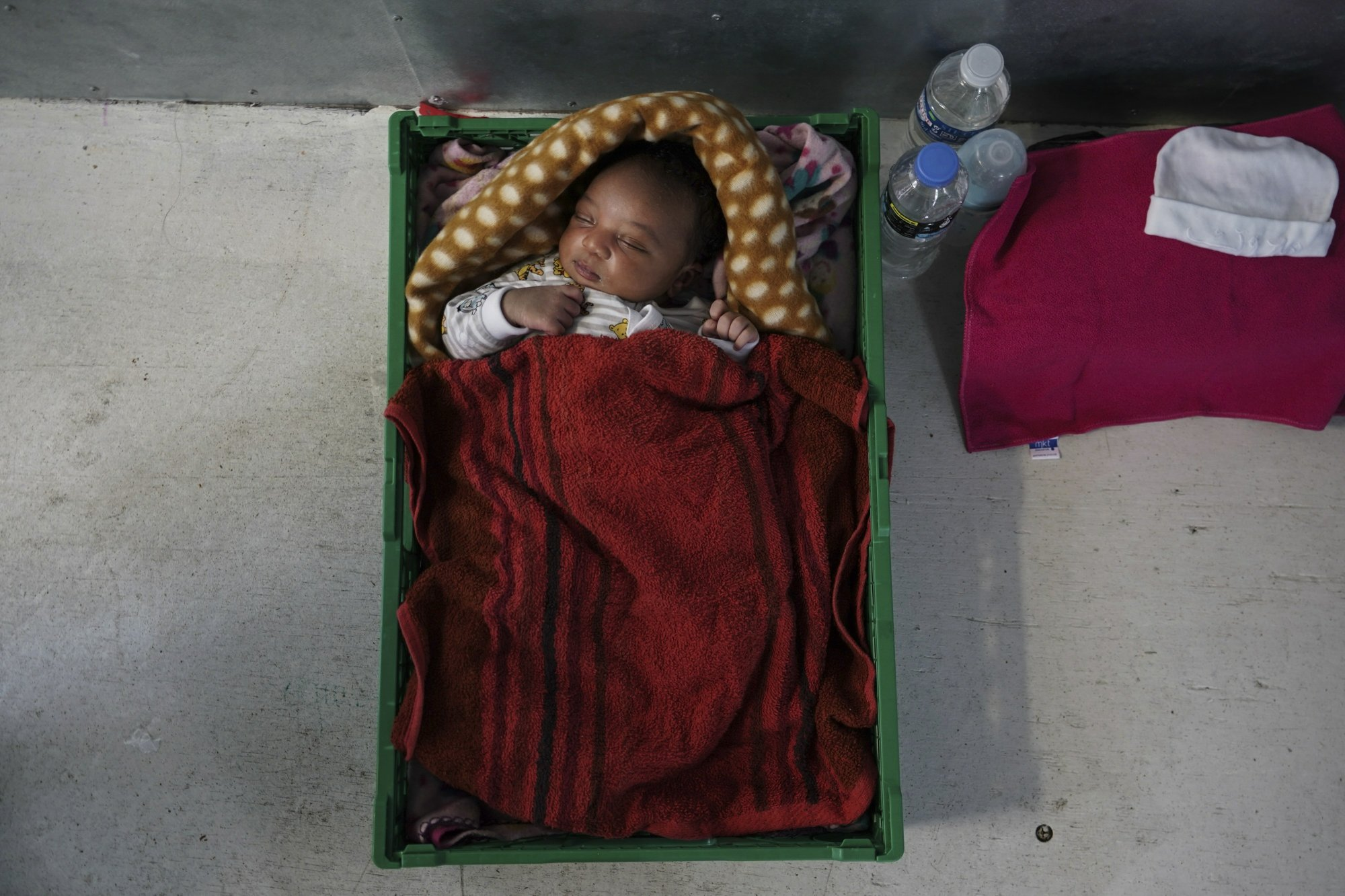 In this Sept. 18, 2019 photo, newborn baby Ange sleeps in a makeshift crib aboard the Ocean Viking humanitarian ship as it sails in the Mediterranean Sea. His mother, Prudence Aimee, gave birth to her third son Sept. 13, just three days before boarding an overcrowded wooden boat in the hope of getting her children out of war-torn Libya. Her husband was not able to join them and stayed behind. (AP Photo/Renata Brito)