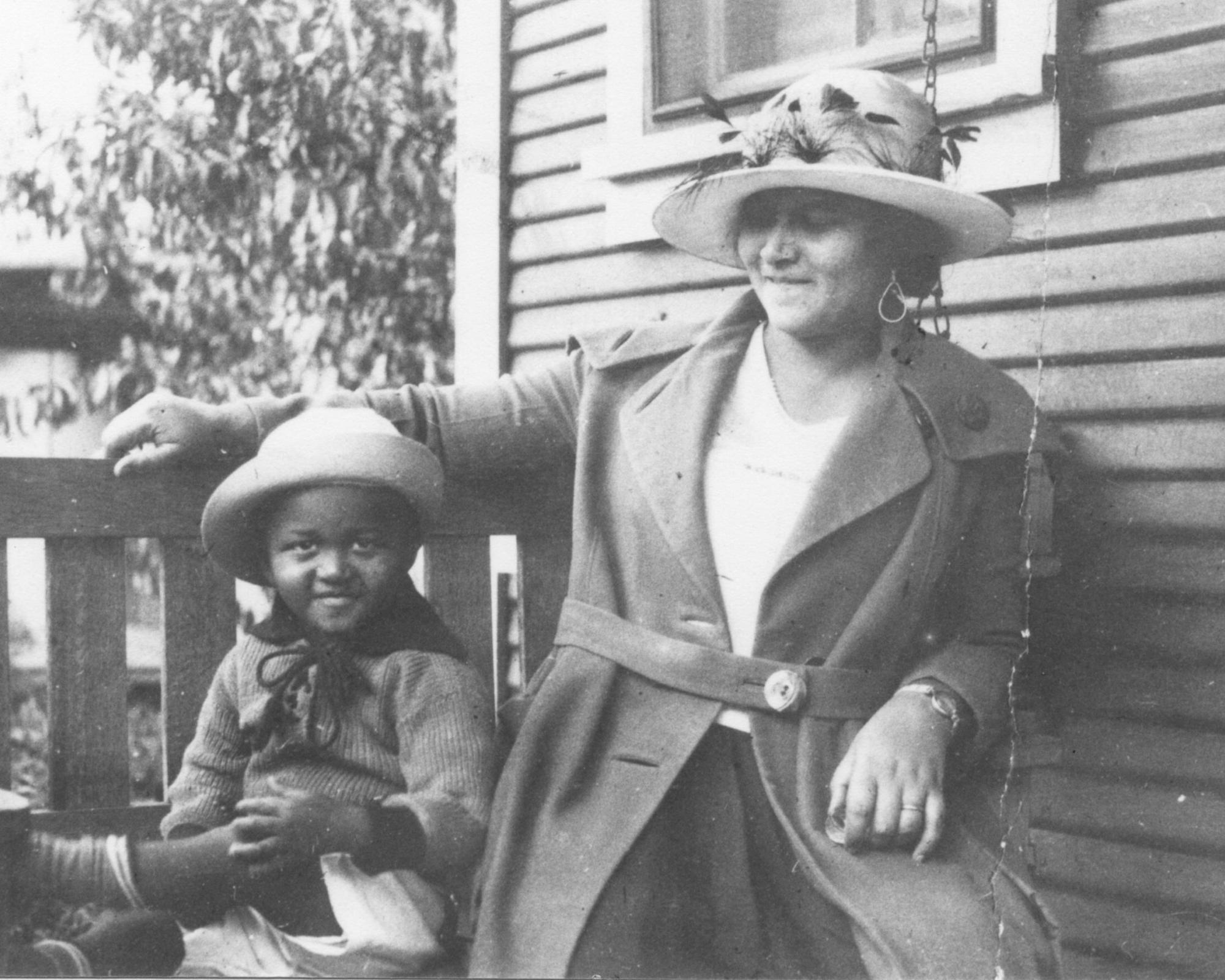 This photo provided by the Department of Special Collections, McFarlin Library, The University of Tulsa shows an African American woman and girl sitting on a porch swing, both dressed in coats and hats, by the side of a house. Provenance is unknown; however, it is believed that these photos were taken in Tulsa, Okla. prior to the Tulsa Race Massacre. (Department of Special Collections, McFarlin Library, The University of Tulsa via AP)