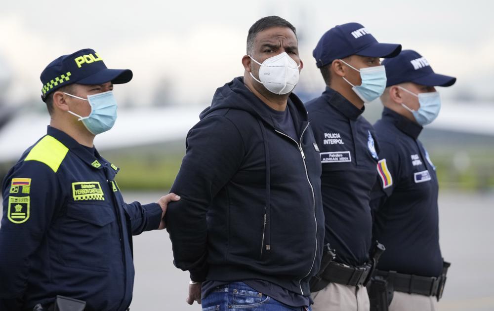 El exparamilitar Alexánder Montoya Úsuga es escoltado por la policía antes de su extradición a Estados Unidos en el aeropuerto militar CATAM en Bogotá, Colombia, el jueves 19 de agosto de 2021. Usuga es buscado en Florida por cargos relacionados con el tráfico de drogas. (AP Foto/Fernando Vergara)