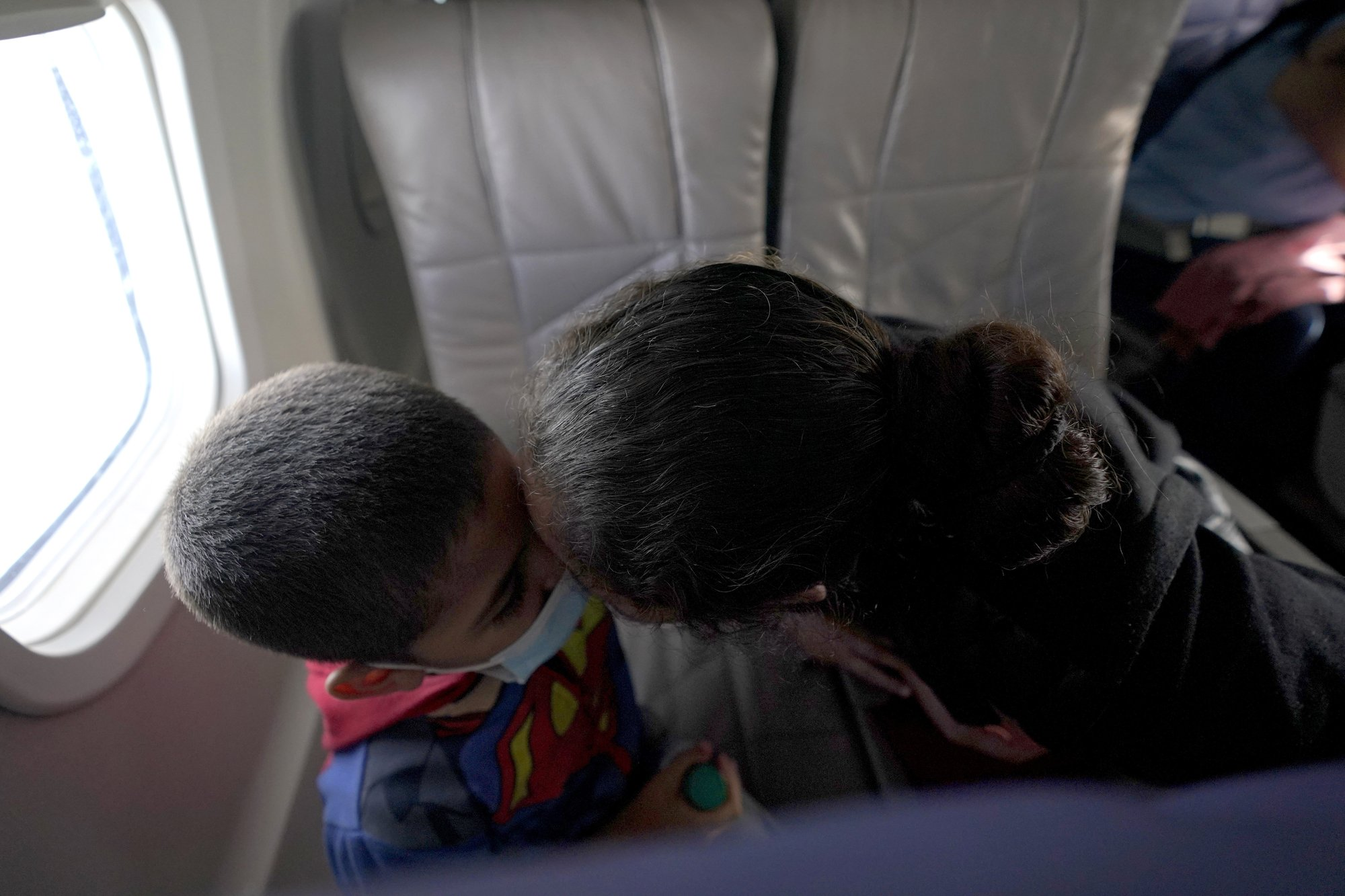 Honduran boy and mother on flight from Harlington to Houston then to Baltimore to be with family after border detention
