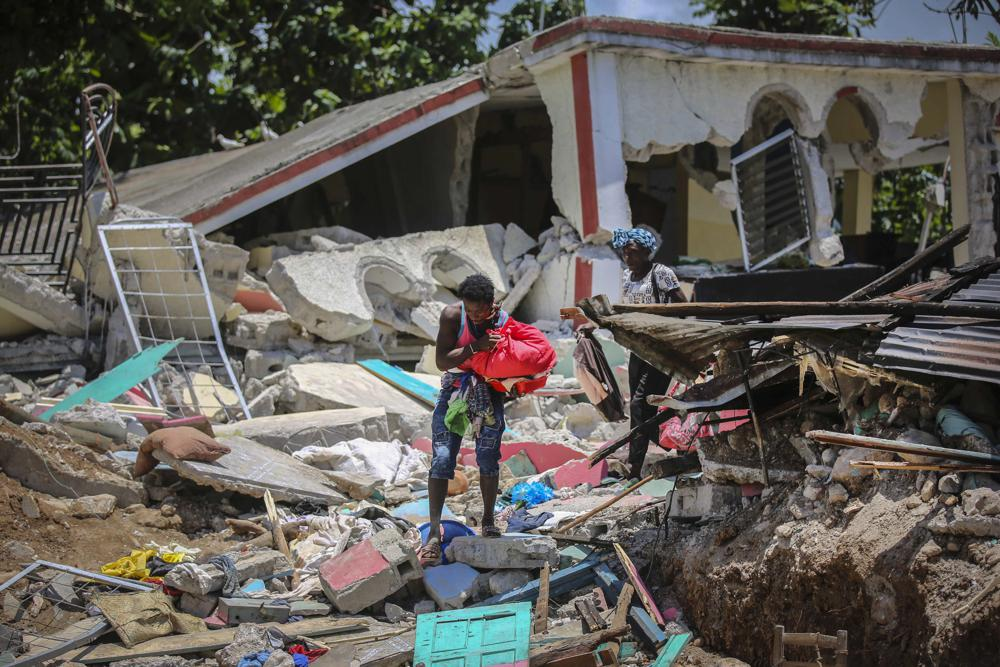 Locals recover their belongings from their homes destroyed in the earthquake in Camp-Perrin, Les Cayes, Haiti, Sunday, Aug.  15, 2021. The death toll from the magnitude 7.2 earthquake in Haiti soared on Sunday as rescuers raced to find survivors amid the rubble ahead of a potential deluge from an approaching tropical storm.  (AP Photo/Joseph Odelyn)