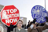 FILE - In this Nov. 30, 2005 file photo, an anti-abortion supporter stands next to a  pro-choice demonstrator outside the U.S. Supreme Court in Washington.  The new poll from The Associated Press-NORC Center for Public Affairs Research finds 61% of Americans say abortion should be legal in most or all circumstances in the first trimester of a pregnancy. However, 65% said abortion should usually be illegal in the second trimester, and 80% said that about the third trimester.  (AP Photo/Manuel Balce Ceneta)