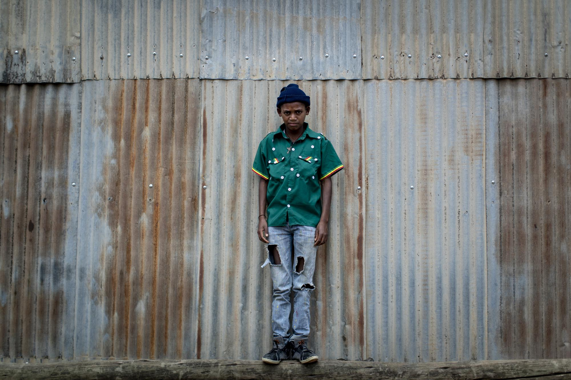 Gebremedhin Gebreslassie, 12, who fled from fighting in the town of Hawzen, stands next to a metal shack at a reception center for the internally displaced in Mekele, in the Tigray region of northern Ethiopia, on Sunday, May 9, 2021. Residents of Hawzen, a town of a few thousand people, said it had seen fighting four times since November. (AP Photo/Ben Curtis)
