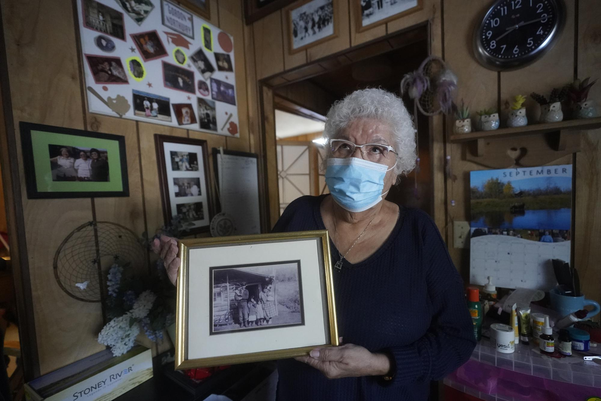 """Daisy Northway holds an undated photograph of her parents at her home Wednesday, Sept. 22, 2021, in Tok, Alaska. Northway speaks from first-hand knowledge when advocating that people get vaccinated for COVID-19. Her family came from Healy Lake, located about 70 miles northwest of Tok. The small village's population was almost entirely wiped out by a smallpox epidemic in 1947. """"My mother and dad had to bury my mother's parents and three of their children in a mass grave because they were so tired,"""" she said. (AP Photo/Rick Bowmer)"""