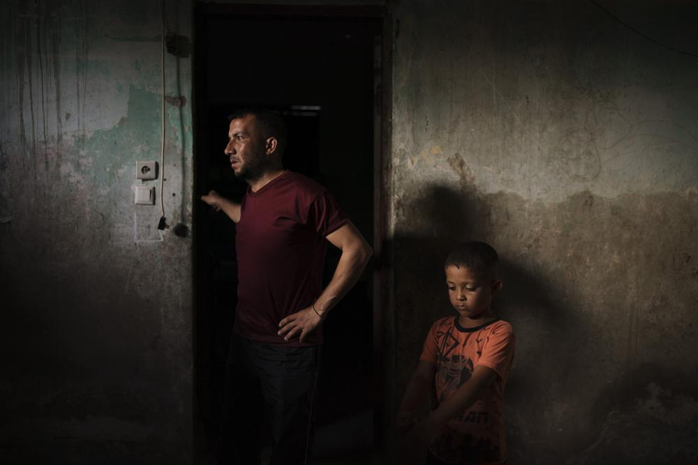 Jalal Nassir stands with his son in their home, damaged in the recent 11-day war between Israel and Hamas, the militant group that controls Gaza, in Beit Hanoun, northern Gaza Strip, Saturday, June 12, 2021. Four wars since 2008 have done about $5 billion in damage to Gaza's buildings, roads, electrical and water systems, close to double the Strip's annual economic output. Nearly 250,000 homes have been damaged or destroyed. (AP Photo/Felipe Dana)
