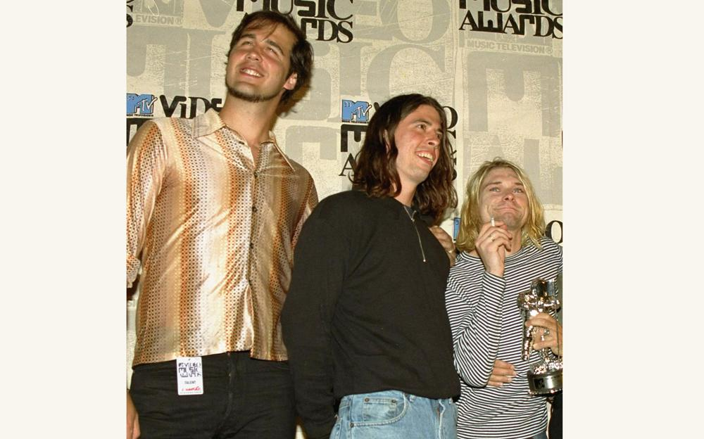 """FILE - Nirvana band members Krist Novoselic, from left, Dave Grohl and Kurt Cobain pose after receiving the award for best alternative video for """"In Bloom"""" at the 10th annual MTV Video Music Awards on Sept. 2, 1993, in Universal City, Calif. A 30-year-old man who appeared nude at 4 months old in 1991 on the cover of Nirvana's """"Nevermind"""" album is suing the band and others, alleging the image is child pornography they have profited from. The suit, filed by Spencer Elden on Tuesday, Aug 24, 2021, seeks at least $150,000 from each of more than a dozen defendants, including the Kurt Cobain estate, surviving Nirvana members Novocelic and Grohl and Geffen Records. (AP Photo/Mark J. Terrill, File)"""