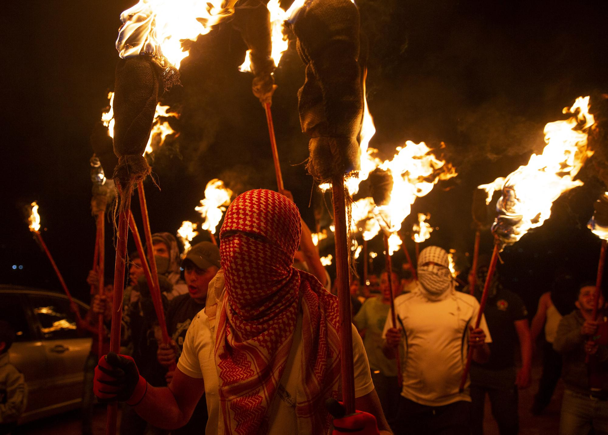 Palestinian demonstrators march with torches during a protest against the West Bank Jewish settlement outpost of Eviatar that was rapidly established the previous month, at the Palestinian village of Beita, near the West Bank city of Nablus, Sunday, June 27, 2021. The Palestinians say it was established on their farmland and fear it will grow and merge with other large settlements in the area. (AP Photo/Majdi Mohammed)